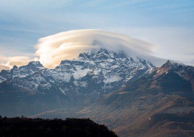 Les nuages lenticulaires, ou altocumulus lenticularis, sont des formations nuageuses présentant des formes rondes ou encore ovoïdes, apparaissant le plus souvent au sommet d'une montagne. Pour se former, trois ingrédients sont nécessaires: une montagne, de l'air chaud et humide ainsi que de puissantes rafales. En remontant un relief, la masse d'air chaud traverse un environnement plus froid et se condense sous forme de gouttelettes d'eau ou de cristaux de glace. Inversement, cette masse d'air redescend sur l'autre flanc, se réchauffe et provoque l'évaporation des gouttelettes d'eau. Ce phénomène provoque donc une oscillation du vent haut/bas (ondes sinusoïdales) entrainant la formation d'un nuage au sommet de l'onde et donc du massif. Ces nuages, à l'aspect très compact et aux colorations parfois très variées, sont des nuages de beau temps et ne donnent jamais de précipitations. Ce phénomène, bien que rare, se manifeste assez fréquemment au-dessus des Dents-du-Midi. Photographie de Roelof Overmeer à Antagnes.