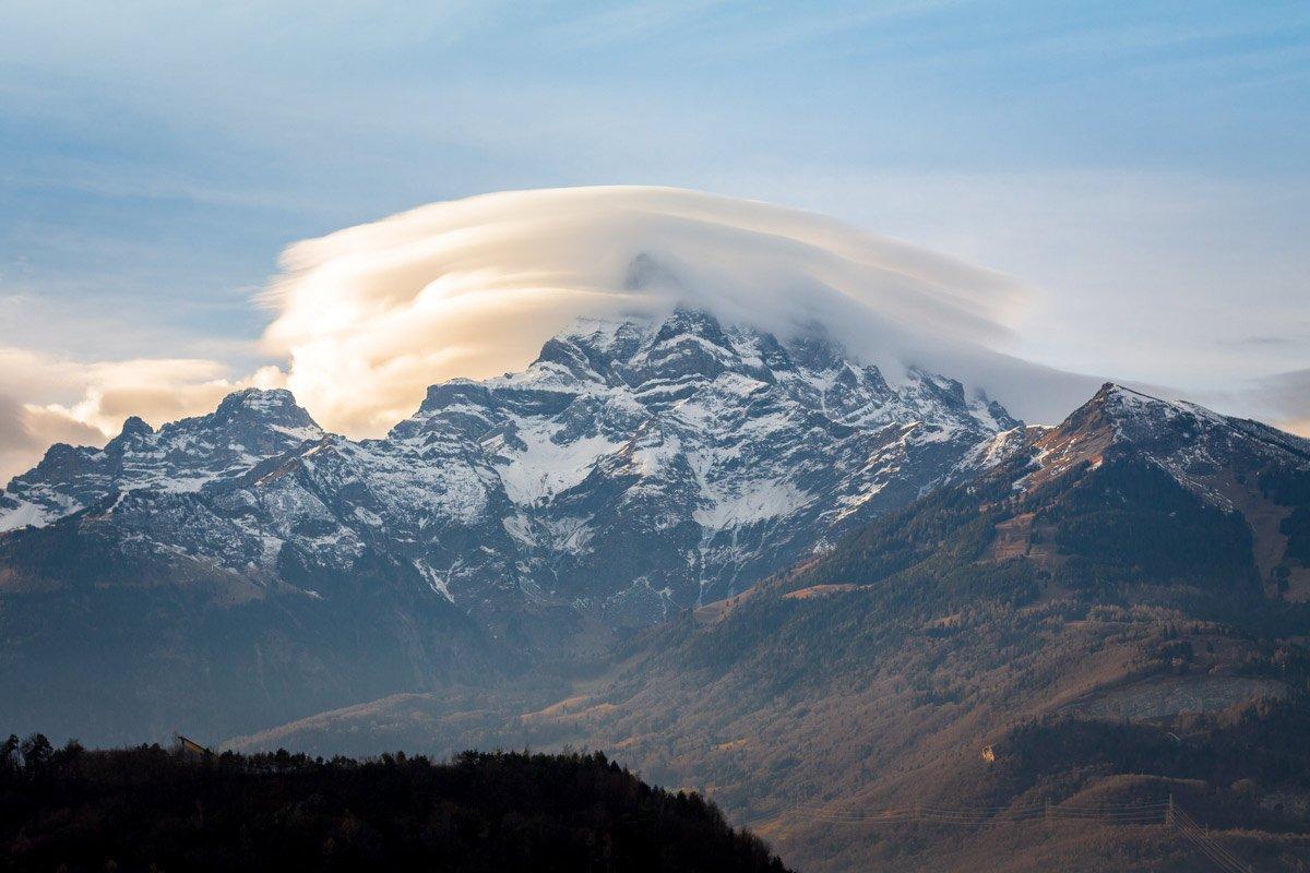 Les nuages lenticulaires, ou altocumulus lenticularis, sont des formations nuageuses présentant des formes rondes ou encore ovoïdes, apparaissant le plus souvent au sommet d'une montagne. Pour se former, trois ingrédients sont nécessaires: une montagne, de l'air chaud et humide ainsi que de puissantes rafales. En remontant un relief, la masse d'air chaud traverse un environnement plus froid et se condense sous forme de gouttelettes d'eau ou de cristaux de glace. Inversement, cette masse d'air redescend sur l'autre flanc, se réchauffe et provoque l'évaporation des gouttelettes d'eau. Ce phénomène provoque donc une oscillation du vent haut/bas (ondes sinusoïdales) entrainant la formation d'un nuage au sommet de l'onde et donc du massif. Ces nuages, à l'aspect très compact et aux colorations parfois très variées, sont des nuages de beau temps et ne donnent jamais de précipitations. Ce phénomène, bien que rare, se manifeste assez fréquemment au-dessus des Dents du Midi. Photographie de Roelof Overmeer à Antagnes