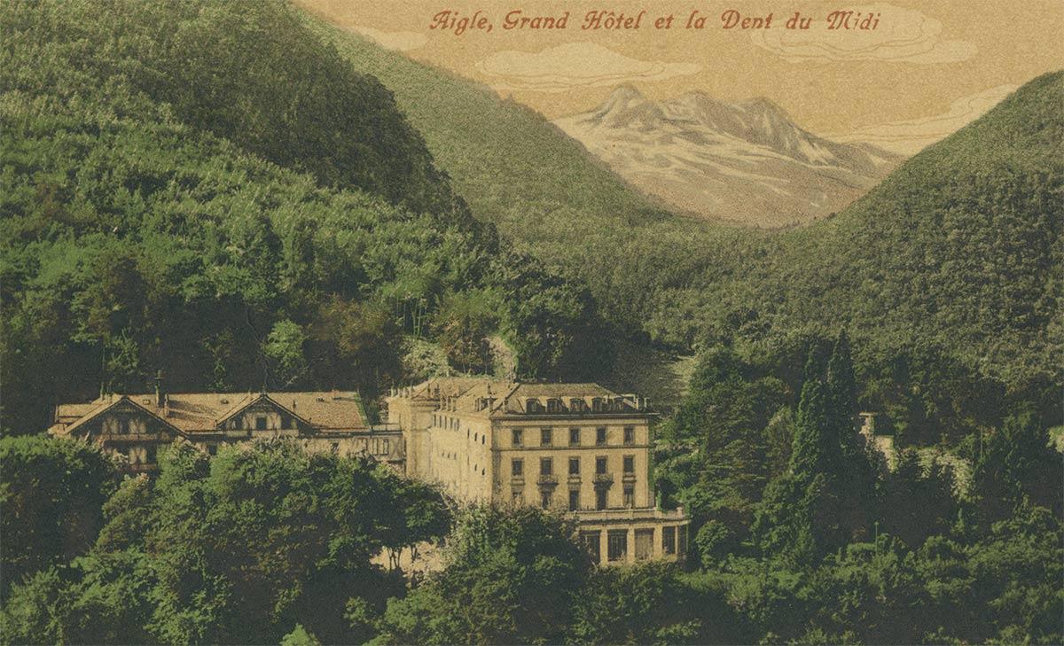 Construit par l'architecte aiglon Louis Bezencenet entre 1871 et 1872, le Grand Hôtel des Bains d'Aigle était destiné à une clientèle étrangère fortunée. De style néo-classique typique du milieu du XXe siècle, l'hôtel était doté de cent vingt-trois chambres et salons. L'utilisation des anciennes salines d'Aigle et des célèbres eaux de Fontanney garantissait à cet hôtel tous les avantages d'un établissement de bains froids et salins des mieux organisés. Les belles forêts de hêtres et de sapins aux portes de l'hôtel et dans lesquelles étaient tracés de nombreux sentiers offraient des promenades toujours ombragées où l'air s'imprégnait de mille odeurs aromatiques et fortifiantes. © Edition Guggenheim & Co., Zürich, carte datée de 1919