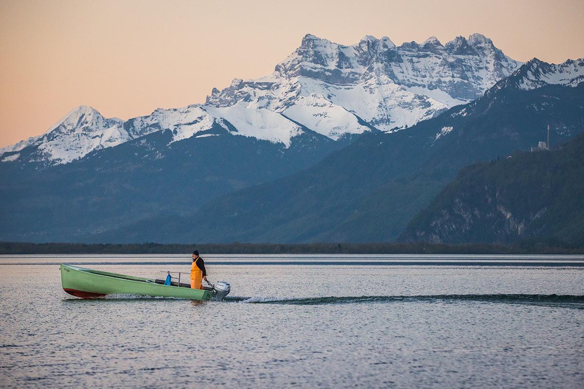 La Tour-de-Peilz, 19 avril 2018, 6 h 35. Profitant d'une plage offerte par un niveau du lac fixé au minimum entre la mi-mars et la mi-avril, je me prépare à photographier le lever du soleil sur les Alpes et les Dents du Midi. Alors que la lumière du soleil n'effleure pas encore les sommets, j'aperçois la venue, depuis le port de Vevey, de ma première barque de pêcheur. Parfait accord d'un moment unique sous la teinte d'un ciel qui me préparait pourtant à l'imminence de l'instant. © Fabrice Ducrest