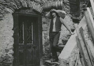 """Salvan - Utilisation du """"paillet"""" pour porter un tonnelet, vers 1920. © Fonds Boissonnas, Bibliothèque de Genève"""