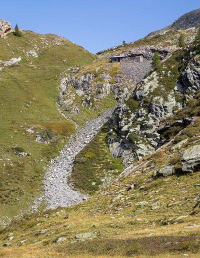Vue de la Cabane des Mines depuis de lac des Ottans. On remarque très bien le dévaloir où les roches inutiles étaient séparées du minerai depuis la cabane. © Fabrice Ducrest