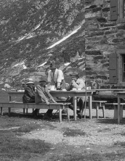 Devant l'auberge de la Cime de l'Est à Salanfe, vers 1924. À la table, de gauche à droite, Jacques Chappuis (1916), Pierre-Yves Abram Chappuis (1914), Pierre-Auguste Chappuis (1888), Louis Chappuis (1887?). Copyright et fonds Philippe Chappuis